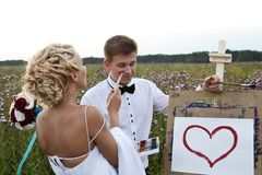 The bride and groom paint on an easel emotion Stock Photography
