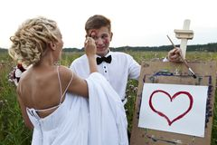 The bride and groom paint on an easel emotion Stock Photos