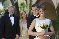 Bride And Groom With Parents In Background Stock Images
