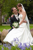 Bride and groom in the park. Beautiful bride and groom together in the park looking happy Royalty Free Stock Photo