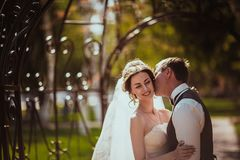 The bride and groom in the park arch.  Royalty Free Stock Photography