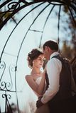 The bride and groom in the park arch.  Stock Photography