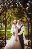 The bride and groom in the park arch.  Stock Image
