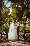 The bride and groom in the park arch.  Royalty Free Stock Photo
