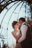 The bride and groom in the park arch.  Royalty Free Stock Image