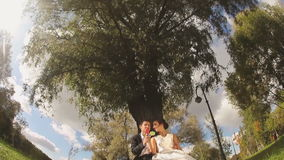 Bride and Groom in the Park with Candies in Hands. Wedding Couple Bride and Groom in the Park Sitting near the Tree with Candies in Hands stock video footage