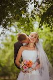 Bride and groom in a park kissing.couple newlyweds bride and groom at a wedding in nature green forest are kissing photo portrait. Stock Image