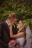 Bride and groom in a park kissing.couple newlyweds bride and groom at a wedding in nature green forest are kissing photo portrait. Royalty Free Stock Photo