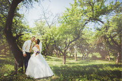 Bride and groom in a park kissing.couple newlyweds    at  wedding in nature green forest are  photo portrait. Stock Photo