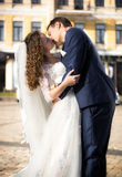 Bride and groom passionately kissing on street at sunny day Stock Photo