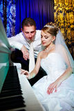 Bride and groom at piano Royalty Free Stock Image