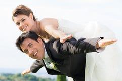 Bride and groom piggyback Royalty Free Stock Photos