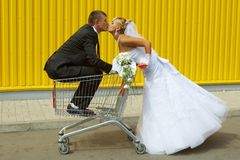Bride and groom playing with a basket of supermarket. Funny bride and groom playing with a basket of supermarket Royalty Free Stock Photo