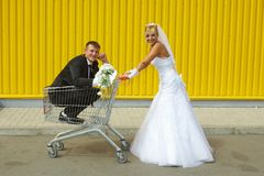 Bride and groom playing with a basket of supermarket. Funny bride and groom playing with a basket of supermarket Stock Photos