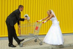 Bride and groom playing with a basket of supermarket Royalty Free Stock Photo
