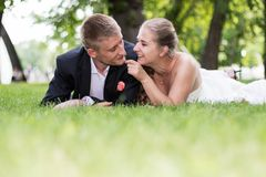 Bride and groom playing in the grass Royalty Free Stock Image