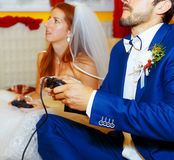 Bride and groom playing together videogames with joysticks - gaming and wedding concept. Stock Photography