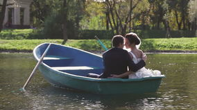 Bride and Groom in the Pleasure Boat. Wedding Couple Bride and Groom in the Park Pond in the Pleasure Boat stock video footage
