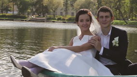 Bride and Groom in the Pleasure Boat. Wedding Couple Bride and Groom in the Park Pond in the Pleasure Boat stock video