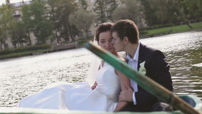 Bride and Groom in the Pleasure Boat. Wedding Couple Bride and Groom in the Park Pond in the Pleasure Boat stock footage