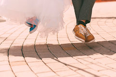 Bride and groom in plimsolls above sett Royalty Free Stock Images