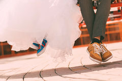 Bride and groom in plimsolls in the air Stock Photo