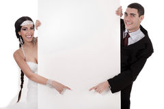 Bride and groom pointing at blank board. Over white background Royalty Free Stock Photos