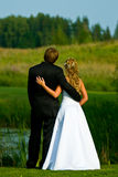 Bride and groom at pond. A view of the back of a bride and groom looking across a pond or small lake royalty free stock photo