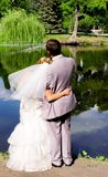 Bride and groom on the pond stock photography