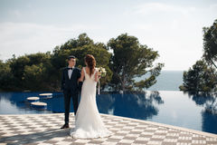 The bride and groom beside the pool with blue water Stock Images
