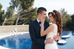 The bride and groom beside the pool with blue water Stock Photography