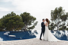 The bride and groom beside the pool with blue water Royalty Free Stock Image