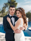 The bride and groom beside the pool with blue water Stock Photo