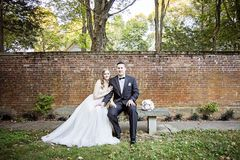 Bride and Groom  portrait in garden. A bride and groom sitting on a bench in front of a brick wall in a garden Royalty Free Stock Image