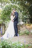 Bride and Groom  portrait in garden. A bride and groom standing under arch on brick patio  in garden Royalty Free Stock Image