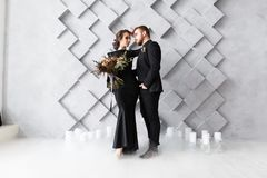 Bride and groom portrait in studio. Isolated on gray geometric background. Dry ice smoke on floor royalty free stock images