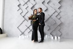 Bride and groom portrait in studio. Isolated on gray geometric background. Dry ice smoke on floor royalty free stock photography