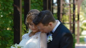 Bride and groom pose to photographer outdoor. Young man gently kiss his bride on the shoulder. Middle plan. Day light stock video footage