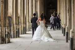 Bride and groom pose for wedding shots under Palais Royal arcade. Bride and groom, seen from behind, pose for photographer under arcade of Palais Royal, Paris Stock Images