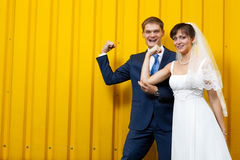 Bride and groom posing against wall Stock Image