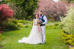 Bride and groom posing in beautiful garden. Full lense classic portrait of young stylish just married couple with pink details on nature green background Stock Photo