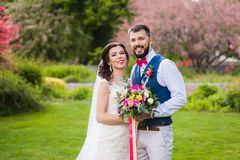 Bride and groom posing in beautiful garden. Portrait of young stylish just married couple with pink details on nature green background Royalty Free Stock Photos