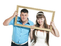 Bride and groom are posing with the big frame Royalty Free Stock Photography