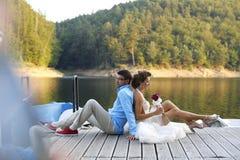 Bride and groom posing on bridge near a lake. Bridal couple sitting on a bridge near the lake Stock Images