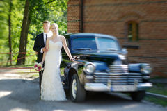 Bride and groom posing by a car Stock Photography