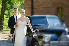 Bride and groom posing by a car Royalty Free Stock Image