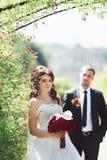 bride & groom posing flower bush in park Royalty Free Stock Photo