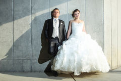 Bride and groom posing in front of wall Royalty Free Stock Image