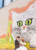 Bride and groom posing near graffiti wall with Royalty Free Stock Image