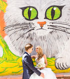 Bride and groom posing near graffiti wall with Stock Photography